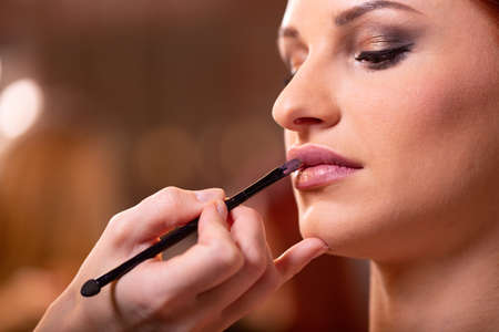 Makeup artist applies red lipstick . Beautiful woman face. Hand of make-up master, painting lips of young beauty model girl . Make up in process Stock Photo - 124756288