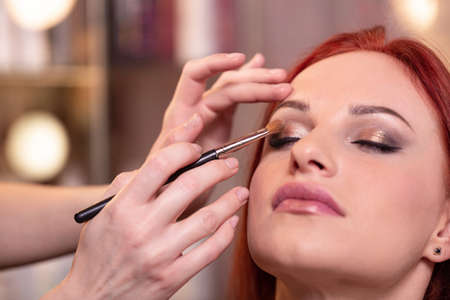 Closeup Of Beautiful Young Woman Face With Beauty Makeup, Fresh Soft Skin And Long Black Thick Eyelashes Applying Mascara With Cosmetic Brush. Make-up And Cosmetics Concept. High Resolution Banque d'images - 124756380