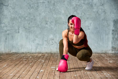 Beautiful young girl boxing gloves near the wall.