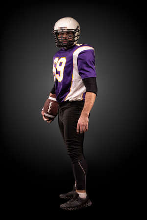 American football player posing with ball on black background Stock Photo - 124754201