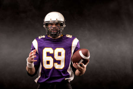 American football player posing with ball on black background Stock Photo - 124754200
