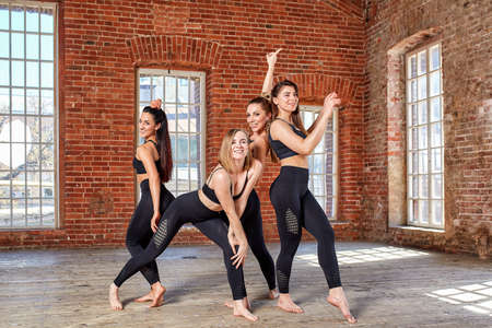 Concept teamwork, movement life, sport, beauty, success. Beautiful fitness girls in a fitness room, having fun before a workout. Stock Photo - 124757214