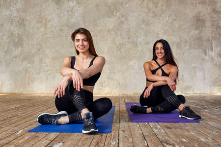 Two smiling beautiful, fitness girls doing exercises in the fitness room on the mats. Concept sport, teamwork.