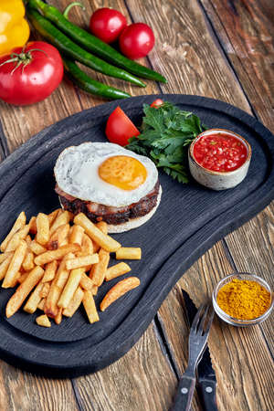 Beef steak with egg and salad from greens and vegetables. Wooden background, table setting, fine dining Stock Photo