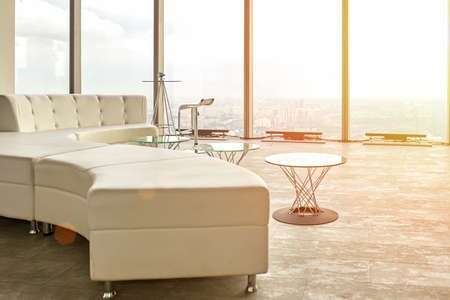 High end design in a skyscraper, a sofa, tables with a view to the view windows and the city