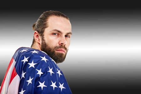 American football concept, portrait of american football player with american flag on black background. Concept patriotism, sport, motivator.