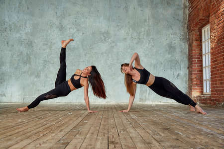 Two beautiful, fitness girls doing paired exercises in a fitness room. Concept sport, teamwork.