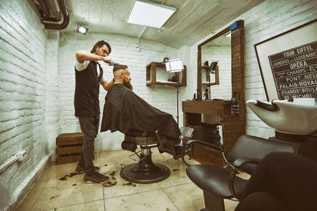 Brutal guy in modern Barber Shop. Hairdresser makes hairstyle a man with a long beard. Master hairdresser does hairstyle by scissors and comb Stok Fotoğraf
