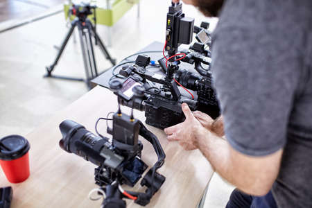 Videographer shooting a film or a television program in a studio with a professional camera, backstage
