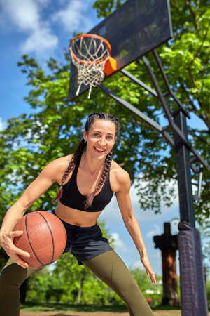 Beautiful sexy fitness girl in black sport wear with perfect body with basket ball at basketball court. Sport, fitness, lifestyle concept Stock Photo