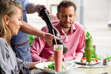 Concept restaurants, guest service. The waiter fills the salad with fresh pepper. Banco de Imagens