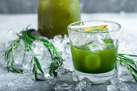 Estragon lemonade. Concept refreshing summer drinks. Fresh cool lemonade tarragon with ice and citrus slices.