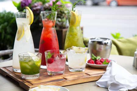 Sommer-Softdrinks, eine Reihe von Limonaden. Limonaden in Krügen auf dem Tisch, um die herum die Zutaten angeordnet sind.