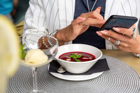 A girl makes selfie food while having lunch in a restaurant. Close-up copy space.
