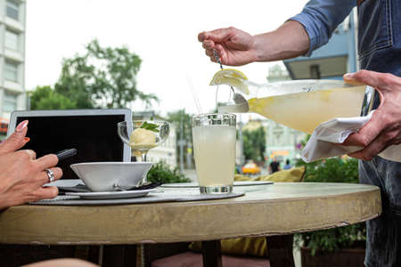 The waiter pours water with lemon and mint into glasses on a serving table. Stock Photo