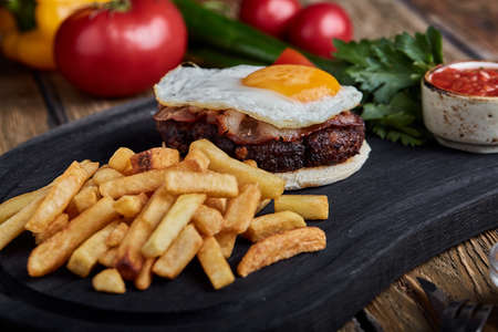 Beef steak with egg and salad from greens and vegetables. Wooden background, table setting, fine dining Imagens