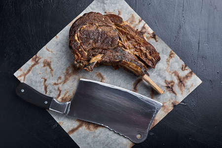Tomahawk steak with vegetables and a knife on the table. Grilled meat with grilled vegetables and fresh vegetables on the table. Stock Photo