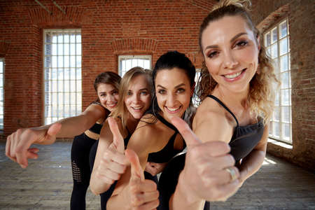Diverse funny girls together in circle on rubber mats wearing sportswear smiling show yoga greeting gesture, looking at camera, top above view. Namaste, symbol of salutation and valediction Imagens