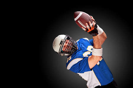American football player in motion with the ball on a black background with a light line, copy space. The concept of the game is American football, movement. Фото со стока