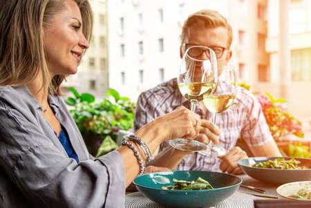 Glückliche Liebhaber, attraktive Frau und Mann genießen die Romantik. Attraktive Paare, die selfie machen, lächeln und zusammen Spaß haben. Ein Paar, das Salate isst, Wein trinkt und Fotos macht. Standard-Bild