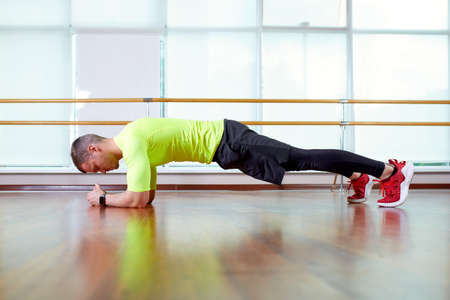 Plank it Confident muscled young man wearing sport wear and doing plank position while exercising on the floor in loft interior Stock Photo