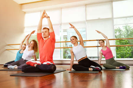 Happy multiracial group of young, smiling beautiful girls and panes in sportswear, doing yoga exercises in the lotus position. Yoga class or fitness. Group fitness concept, group workouts, motivation.