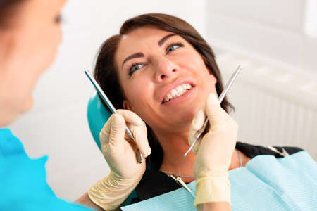 Putting dental braces to the womans teeth at the dental office. Dentist examine female patient with braces in dental office. Close-up of a young attractive girl with braces on the teeth