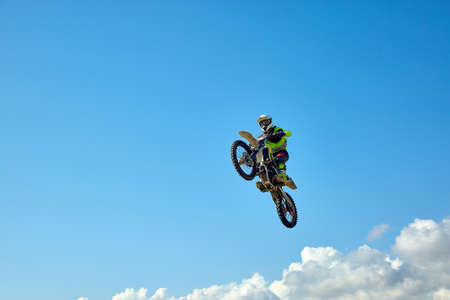 Biker does the trick and jumps in the air. Extreme concept, adrenaline. Copy space. Sky background