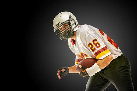 American football player posing with ball on black background. Super Bowl concept. Concept American football, portrait American, Motivator. Black white background, copy space.
