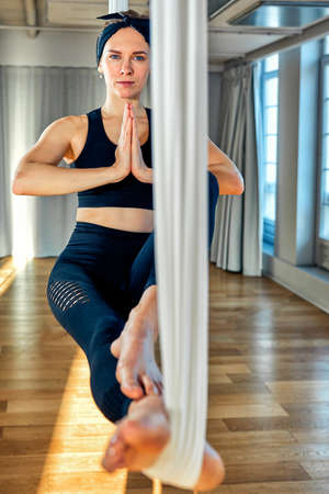 Aerial yoga A beautiful girl aerial yoga trainer shows a variety of exercises on hanging lines in a yoga room. Concept yoga, flexible body, healthy lifestyle, fitness. 免版税图像