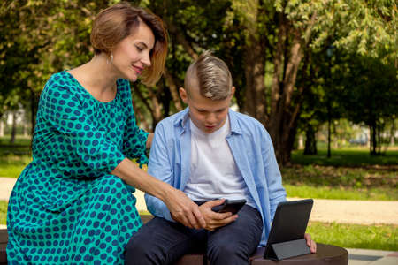 Mom and son using tablet and smartphone while sitting on nature. The family plays computer or searches the Internet, electronic devices and children in modern life.