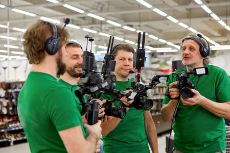 The concept of creating video content, a group of professional operators confer on the plans for shooting. Becktage TV show filming process Stock Photo