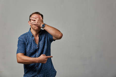 A man in casual clothing hides his face with his hands on a gray background. Emotional, brave face. Isolated on white background Copy space Advertising and commercial design.