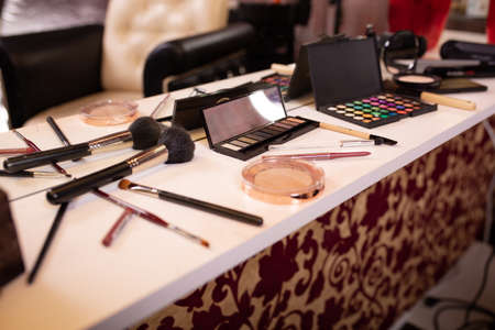 Set for make up. Make-up table with brushes, mascara, corrector, pudding spread out on it.