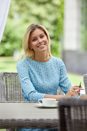 Business woman smiling with coffee at a table on the summer terrace. Copy space, green background.