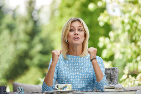 Business woman is sitting in tension with coffee at a table on a summer terrace. Copy space, green background. 版權商用圖片