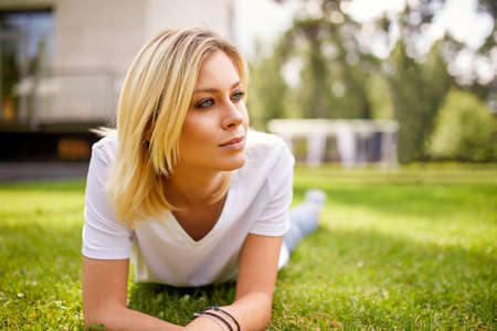 Beautiful young woman smiling at camera in a park outdoors. Outdoor recreation, happy life.