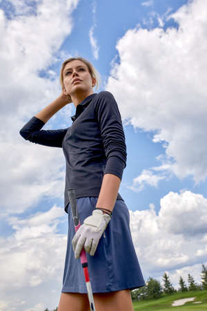 Portrait of a beautiful woman playing golf on a green field outdoors background. The concept of golf, the pursuit of excellence, personal excellence, royal sport.