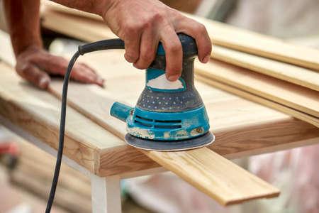 Grinder worker polishes a wooden board. Sanding boards Orbital eccentric machine.