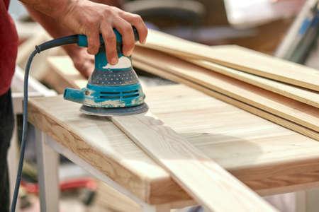 Trabajador de la amoladora pule una tabla de madera. Tablas de lijado Máquina excéntrica orbital. Foto de archivo