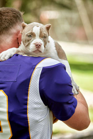 American football player with a dog posing on camera in a park. Copy space, sports banner. Concept american football, sport for the protection of animals. 版權商用圖片
