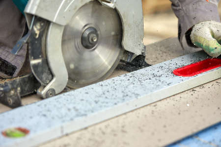 A construction contractor worker using a worm-driven hand-held circular saw to cut boards and plastic. Construction concept, own workshop, hiring a working contract for cutting wood. 版權商用圖片