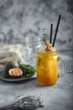 Tropical cocktail with passion fruit, lime and mint on a gray background. 版權商用圖片