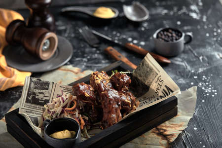 Tasty grilled ribs seasoned with spicy sauce and chopped fresh vegetables on an old rustic wooden cutting board with mustard