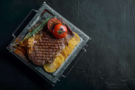 Grilled steak with knife and fork carved on black stone slate. Steak on a hot marble stone. Copy space, dark background, food fashion photo.