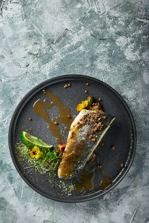 Grilled seabass with eggplant and lime. Horizontal top view, top shot. Copy space, gray concrete marble background, soft light. Food Fashion Photo. 版權商用圖片