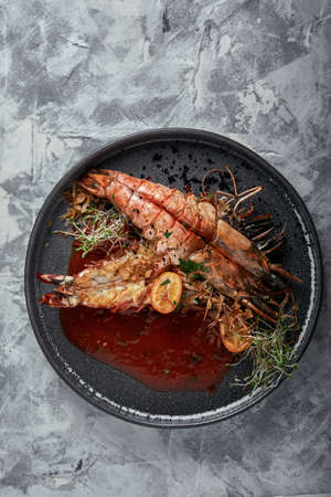 Grilled king prawns, with tomato sauce on a gray background, low key.