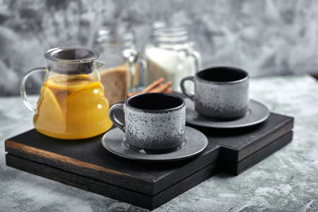 Transparent glass teapot with chitrus tea and cups, tea set on a wooden table. Close up, gray background, soft light.