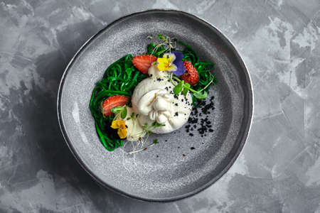 Burrata salad with strawberries and seaweed, on a gray background. Salad with buratta cheese on a gray plate and concrete marble background. 版權商用圖片