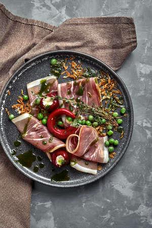 Italian prosciutto crudo and jamon with rosemary. Raw ham on a concrete gray background.